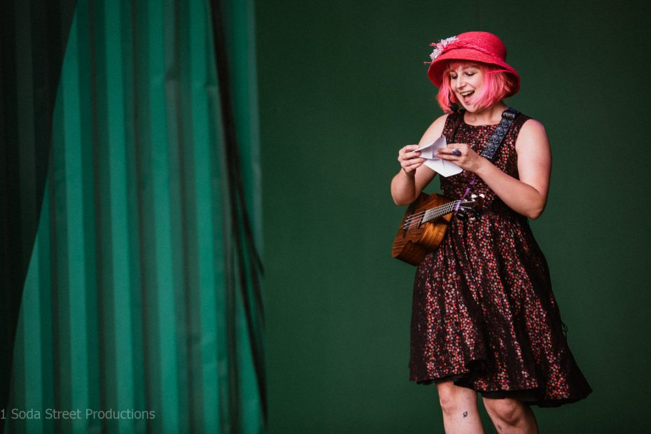 Phi stands on stage wearing her ukulele Willow and reads from an aeroplane love letter