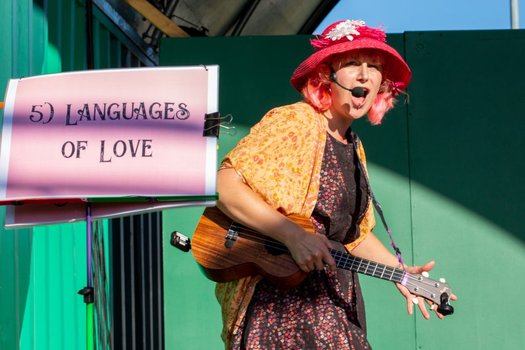 """Phi onstage at """"The Lark"""", Gluttony in Fringe 2021. Beside her a flipchart reads """"Languages of Love"""" and she stands with an expression on her face not unlike a gameshow host trying to encourage people to come on down and get involved!"""